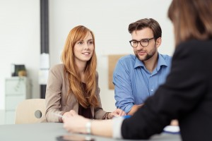 stock-photo-young-married-couple-in-a-meeting-with-a-broker-or-agent-with-focus-to-the-attractive-redhead-wife-281086493